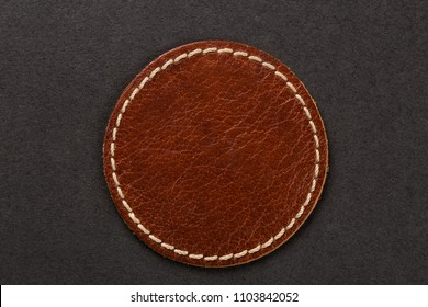 Brown round circular leather label on black background, macro close up