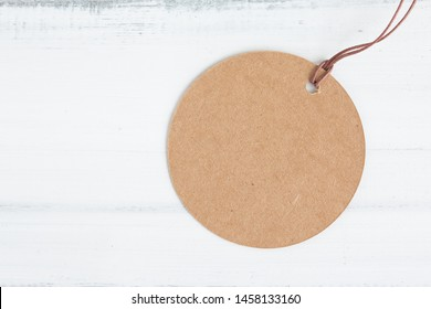 Brown round craft paper label on white wood table over white brick background with copy space.