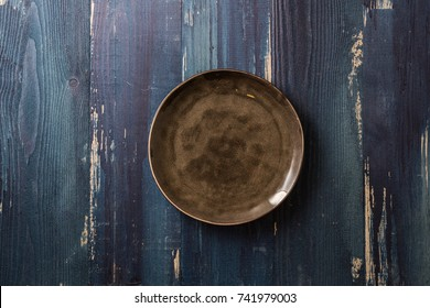 Brown Round Plate on ocean blue wooden table background