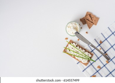 Brown rye crispy bread (Swedish crackers) with spread cottage cheese, decorated with thin green onion, on piece of cloth on white background with space for text, top view. Healthy snack concept