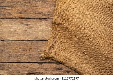 Brown sack Or the background of a natural brown cloth weaving into a bag. For packaging On brown wood panel