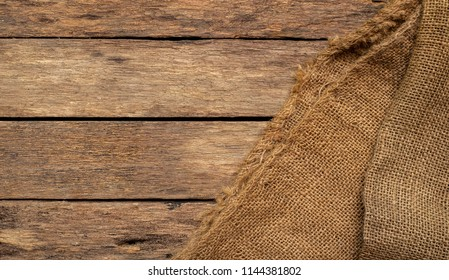 Brown sackcloth Or the background of a natural brown cloth weaving into a bag. For packaging On brown wood panel