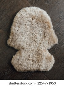 brown sheepskin fur carpet on wooden background