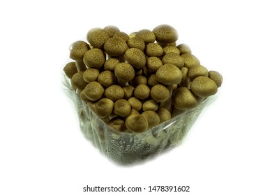 brown shimeji mushrooms in a plastic container on a white background