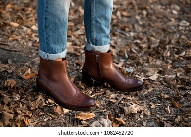 Brown shiny leather womens chelsea boots on woman legs with blue jeans in autumn forest or park.