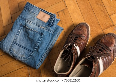 Brown shoes and blue jeans lie by on the floor.