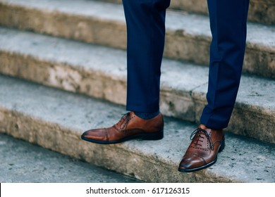 Brown shoes on male legs. The groom in a blue pants.