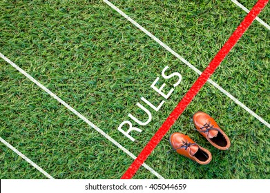 brown shoes standing on the grass field with the word rules  The concept of 'rules'