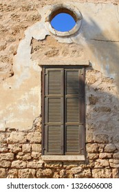 Brown shuttered windows in old wall and blue sky view through hole, Neve Tzedek quarter, Tel Aviv