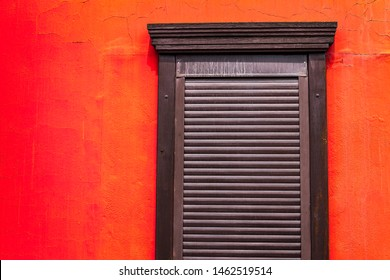 brown shutters on a wooden window on a wall painted in bright red-orange color