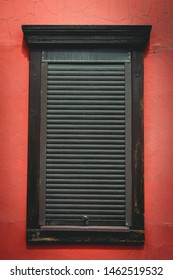 brown shutters on a wooden window on a light burgundy wall; vertical orientation of the photo
