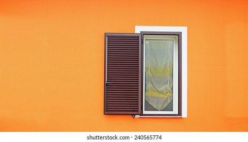 brown shutters in an orange wall