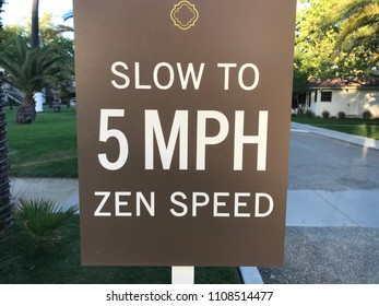 "Brown sign with words ""slow to 5 MPH Zen speed"" in white font. Road behind sign greenery in background."