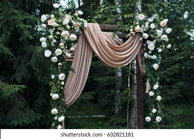 Brown silk cloth hangs from wooden wedding altar decorated with roses