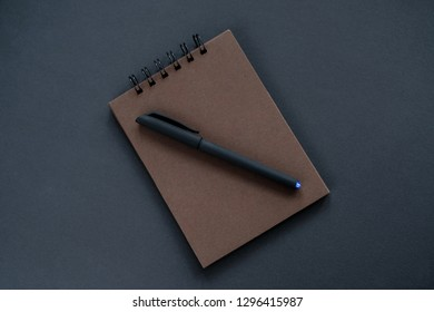 A brown sketchpad, a black pen on a black background