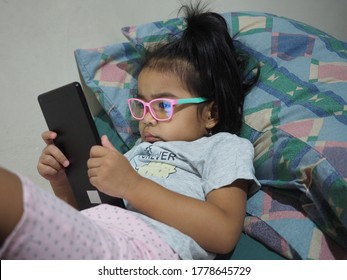 A brown skin Asian kid girl wearing anti-radiation glasses while watching a mobile tablet device