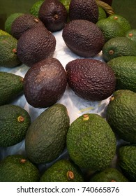 Brown skin avocados surrounded by green color avocados on display.