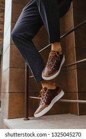 Brown sneakers or shoes with white sole and dark blue pants on men's lags close up. industrial background
