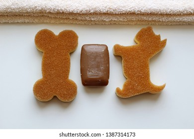 A brown soap bar, a beige towel and two washcloth in the form of a dog and a bone. Soap making. Soap bars. Spa, skin care.