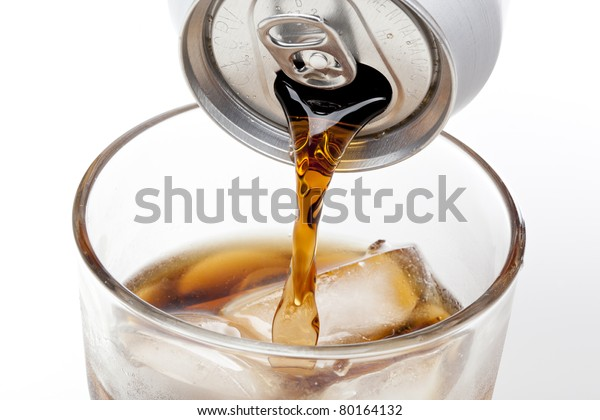 Brown soda in a clear glass against a white background