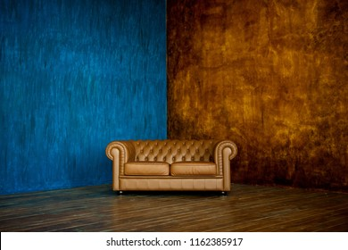 brown sofa chester on a background of blue and brown walls.