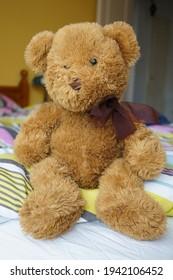 Brown soft teddybear sitting on a bed