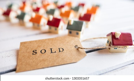 Brown SOLD stamped text label tag with miniature houses on wooden white board. Conceptual image. Selective focus.