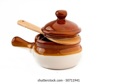 Brown soup crock with wooden spoon on white background