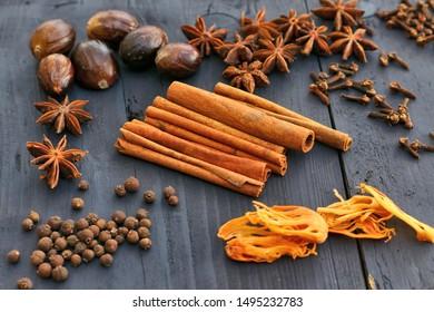 Brown spices on wooden background. Cinnamon sticks, nutmeg, cloves, allspice, star anise.