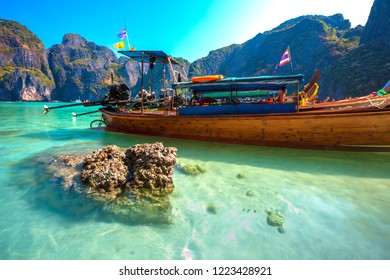 Brown stone in crystal clear transparent turquoise water next to long-tailed boats in a beautiful famous bay on the backdrop of Thai tropical mountains. Maya Bay, Phi Phi Leh island, Krabi, Thailand.