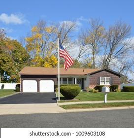 Brown Suburban Ranch home with two car garage blacktop driveway blue sky clouds USA