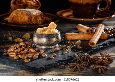 Brown sugar, coffee grains and sticks of cinnamon on a black plate from slate