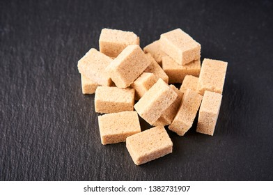 Brown sugar cubes on black background. Brown sugar lump, loaf-sugar. Side view, copyspace, space for text