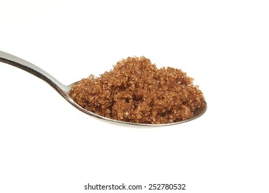 Brown sugar on a teaspoon on a white background