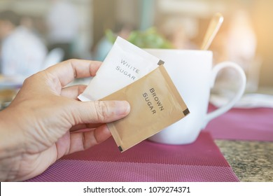 brown sugar packet in hand with blurred coffee cup in coffee shop