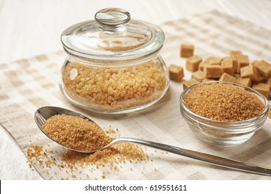 Brown sugar in spoon and dishware on napkin