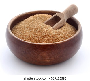 Brown sugar in wooden bowl over white background