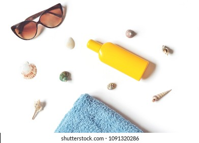 Brown sunglasses, yellow sunscreen bottle, seashells and blue towel on a white background. Flat lay beach essentials. Top view beauty photo