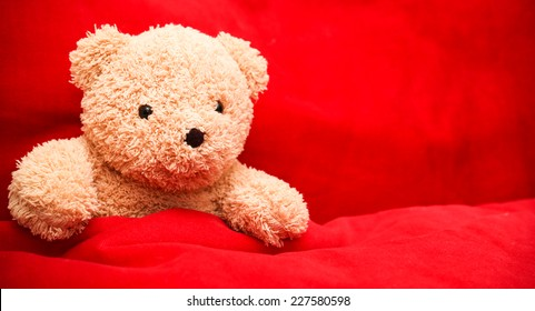 Brown teddy bear alone on red bed
