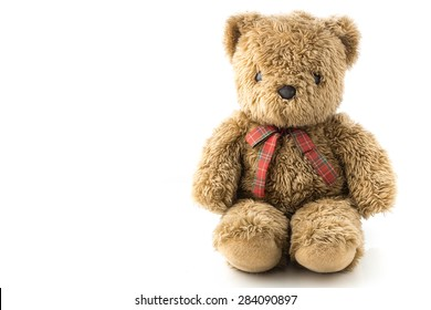 A brown teddy bear doll with red and green ribbon on its chest in white isolation.