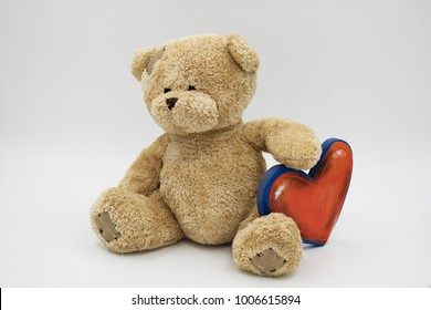 brown teddy bear holding red and blue heart