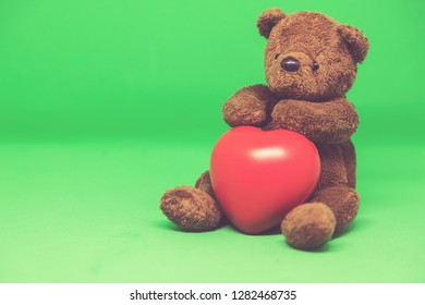 Brown Teddy Bear holding red heart in green background with empty space