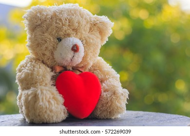 Brown teddy bear holding a red heart on a wooden table with green background bokeh, Valentine day idea.