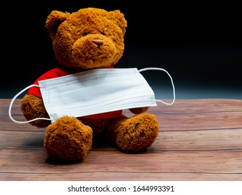 brauner Teddybär auf rotem Hemd, der eine chirurgische Maske zum Schutz vor Infektionen auf schwarzem Hintergrund hält