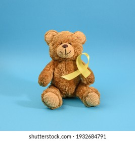 brown teddy bear holds in his paw a yellow ribbon folded in a loop on a blue background. concept of the fight against childhood cancer. problem of suicides and their prevention
