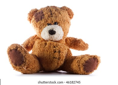 a brown teddy bear with patch on a head sited on white