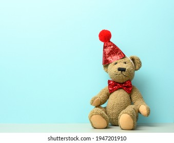 brown teddy bear in a red cap sits on a blue background, place for inscription