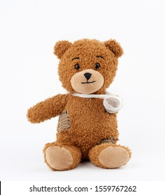 brown teddy bear with rewound white bandage paw on a white background, pediatrics concept