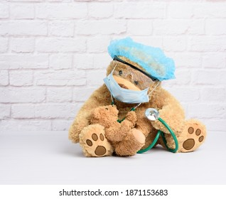 brown teddy bear sits in protective plastic glasses, a medical disposable mask and a blue cap, concept of pediatrics