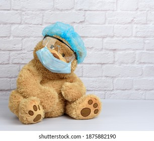 brown teddy bear sits in protective plastic glasses, a medical disposable mask and a blue cap against a background of a white brick wall. Protective accessories from the virus during an epidemic